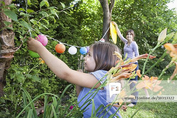 Mutter und Tochter hängen eine Girlande im Garten auf.
