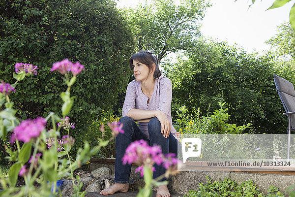 Lächelnde Frau im Garten sitzend entspannt