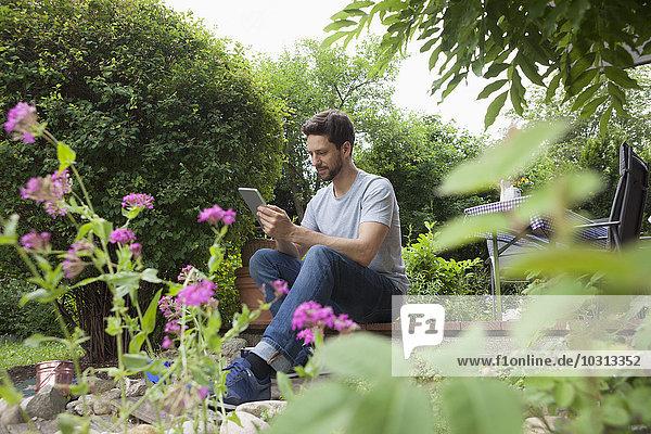 Mann im Garten sitzend mit digitalem Tablett