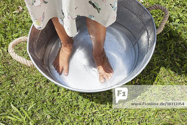 Mädchen beim Fußbad im Zinkeimer Mädchen beim Fußbad im Zinkeimer