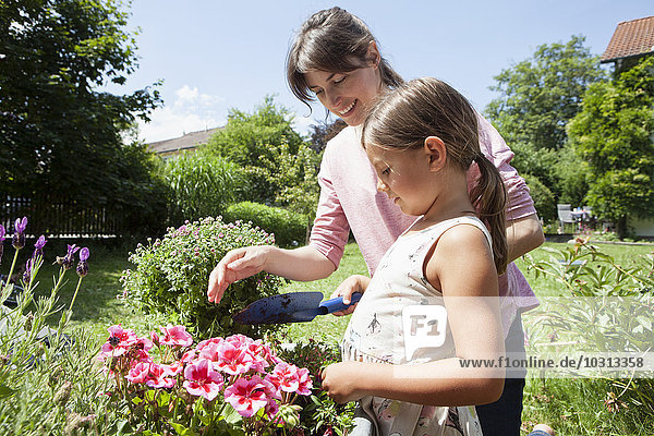 Smiling mother and daughter in garden planting flowers