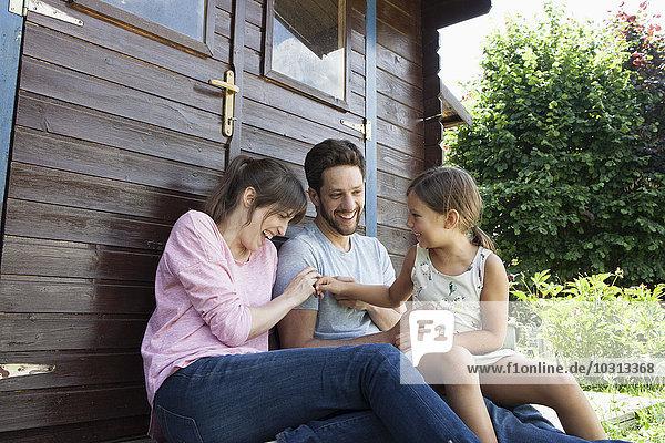 Glückliche Familie mit Tochter im Gartenhaus