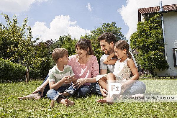 Lächelnde vierköpfige Familie im Garten