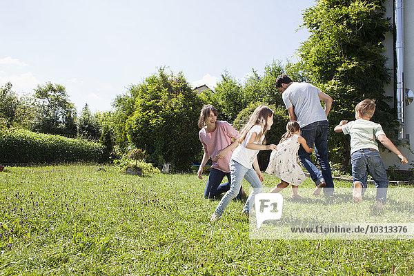 Verspielte fünfköpfige Familie im Garten
