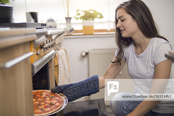 Young woman taking fresh pizza out of oven