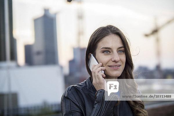 Deutschland  Frankfurt  Porträt einer lächelnden Frau beim Telefonieren mit dem Smartphone