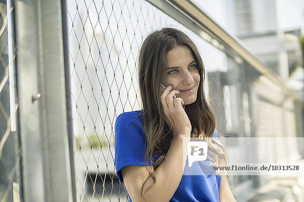Germany  Frankfurt  portrait of smiling woman telephoning with smartphone