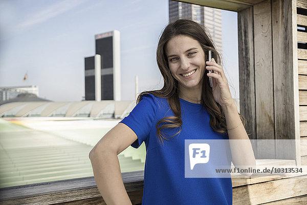 Deutschland  Frankfurt  lächelnde Geschäftsfrau telefoniert mit Smartphone