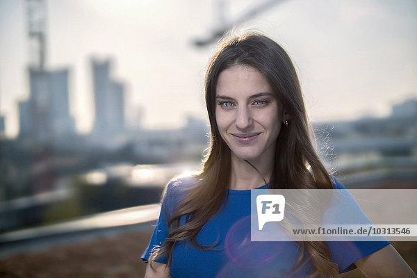 Deutschland  Frankfurt  Porträt einer lächelnden jungen Frau auf der Dachterrasse bei Gegenlicht