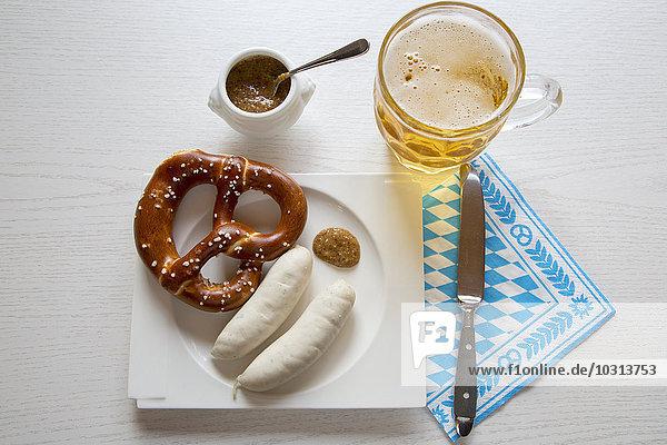 Wurst mit Preztel auf Teller und Bierkrug, süßem Senf, Messer und Serviette