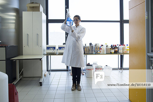 Young female scientist with glass bulb standing in a chemical lab