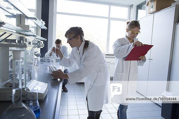 Drei Chemiker  die in einem chemischen Labor arbeiten