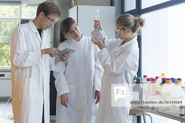 Three chemists working in a chemical laboratory