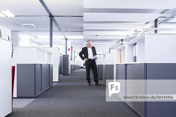 Geschäftsmann im Großraumbüro Lesedokument