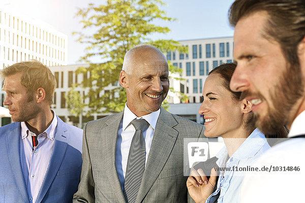 Vier lächelnde Geschäftsleute im Freien