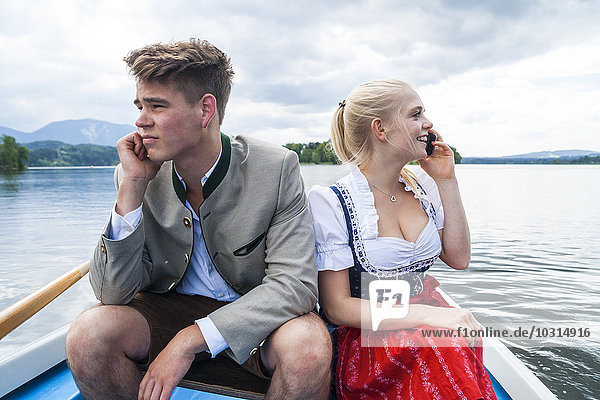Germany  Bavaria  young couple wearing traditional clothes sitting in a rowing boat on Staffelsee