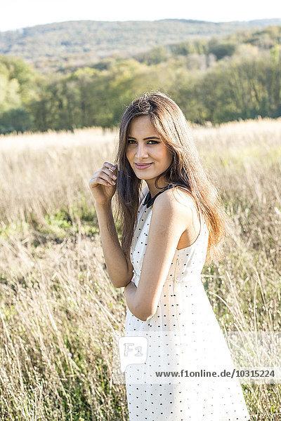 Porträt einer lächelnden jungen Frau im Sommerkleid