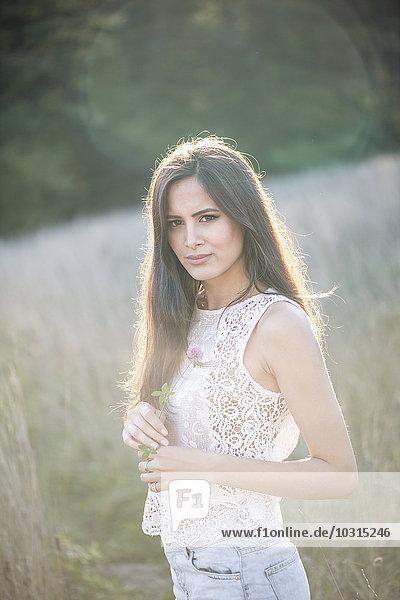 Porträt einer jungen Frau  die im Gegenlicht auf einer Wiese steht.