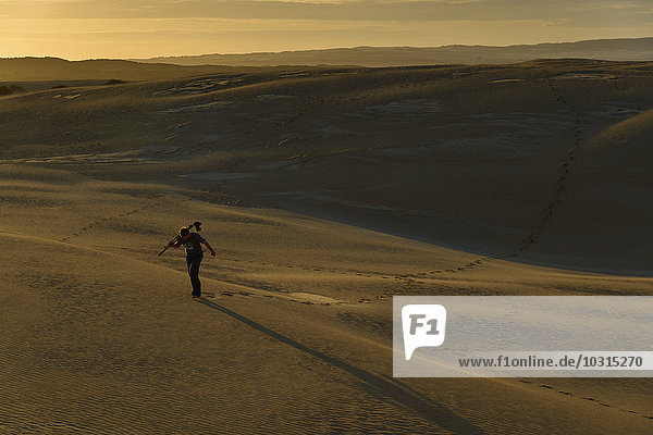 Südaustralien  Mann mit Stativ und Kamera bei Dämmerung durch Sanddünen gehend