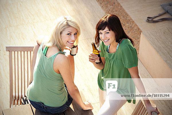 Zwei glückliche Freunde trinken Bier auf der Terrasse Zwei glückliche Freunde trinken Bier auf der Terrasse