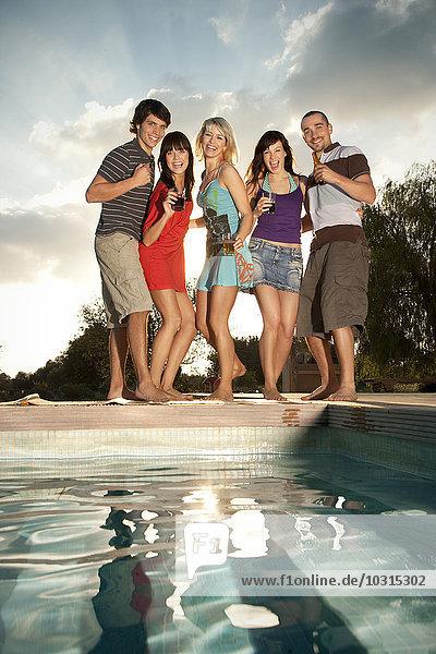 Fröhliche Freunde beim Feiern am Pool