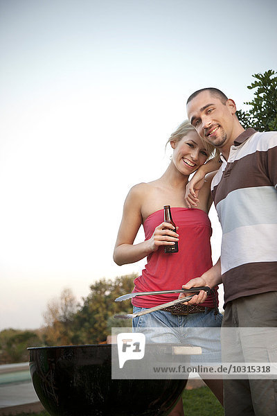 Glückliches junges Paar beim Grillen Glückliches junges Paar beim Grillen