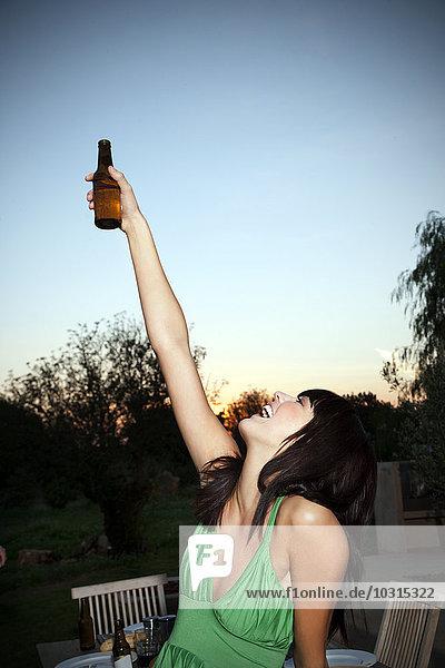 Glückliche junge Frau  die bei Sonnenuntergang ein Bier trinkt. Glückliche junge Frau, die bei Sonnenuntergang ein Bier trinkt.