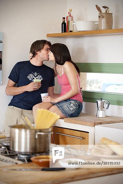 Junges Paar  das sich in der Küche küsst