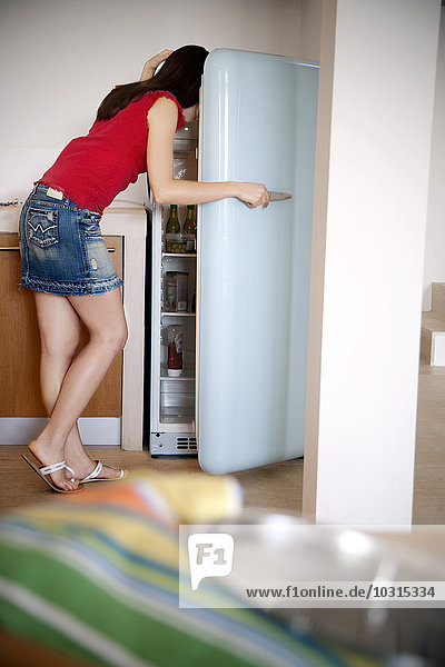 Young woman standing in the kitchen searching something in the fridge