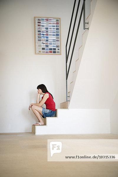 Nachdenkliche junge Frau sitzt auf einer Treppe in einem hellen Raum.