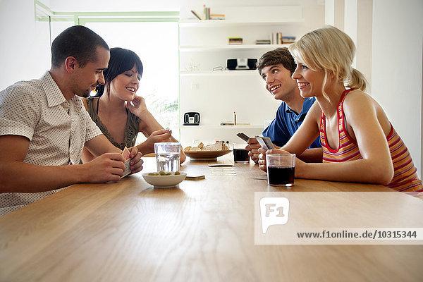Vier Freunde  die zu Hause Karten spielen