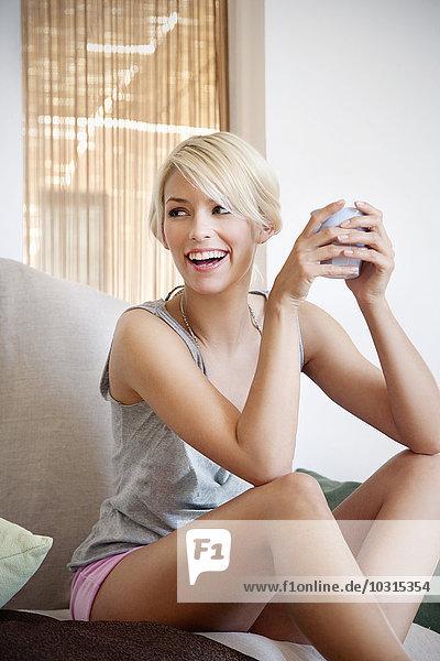 Porträt der lachenden jungen Frau mit Kaffeetasse