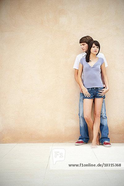 Porträt eines jungen Paares  das sich an die Wand lehnt.