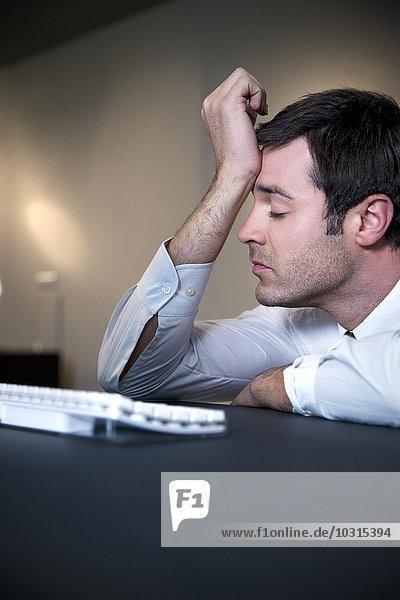 Überarbeiteter Geschäftsmann  der sich auf den Schreibtisch lehnt Überarbeiteter Geschäftsmann, der sich auf den Schreibtisch lehnt