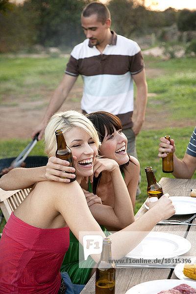 Glückliche Freunde am Gartentisch beim Grillen mit Bierflaschen