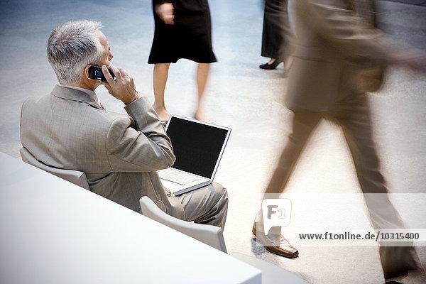 Geschäftsmann mit Handy und Laptop mit vorbeikommenden Personen
