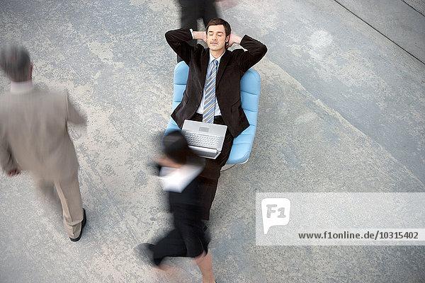 Geschäftsmann mit Laptop bei einer Pause mit vorbeikommenden Menschen Geschäftsmann mit Laptop bei einer Pause mit vorbeikommenden Menschen