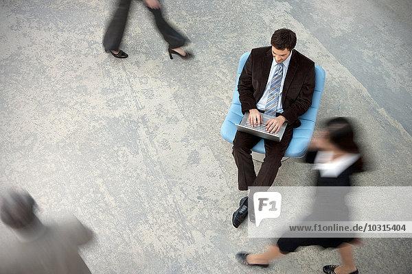 Geschäftsmann mit Laptop und vorbeikommenden Personen