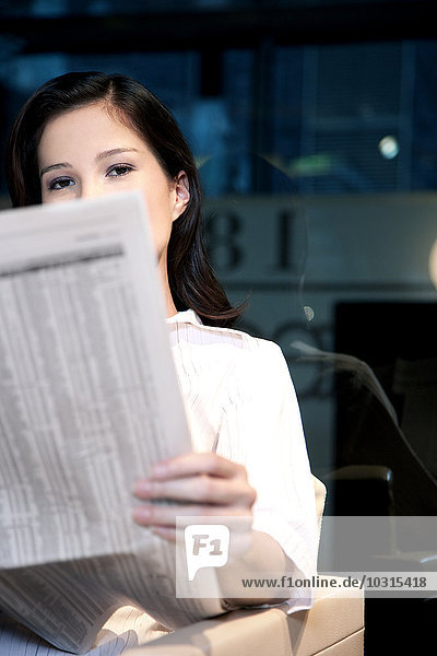 Junge Geschäftsfrau sitzt in einem Sessel und liest Zeitung. Junge Geschäftsfrau sitzt in einem Sessel und liest Zeitung.