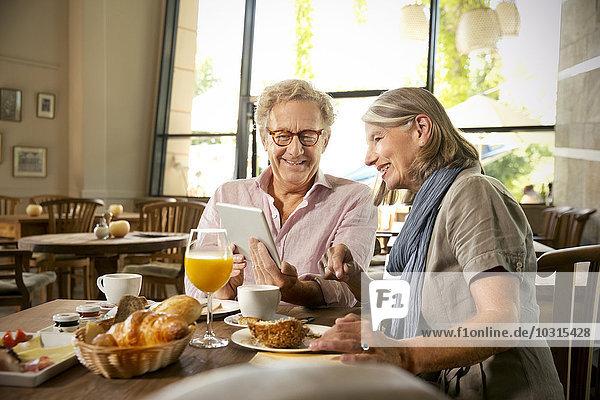 Lächelndes Seniorenpaar mit digitalem Tablett beim Frühstück im Café