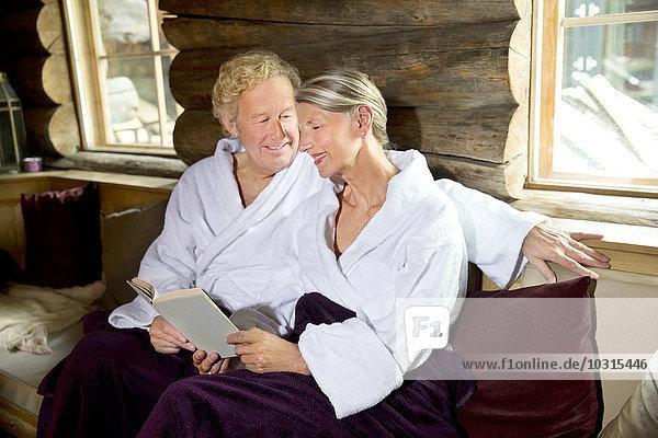 Lächelndes älteres Paar sitzt auf einer Bank im Bademantel und liest ein Buch.