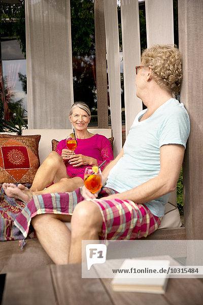 Lächelndes Seniorenpaar sitzt auf der Lounge im Freien mit Cocktails