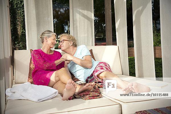 Lächelndes Seniorenpaar im Freien auf der Lounge liegend