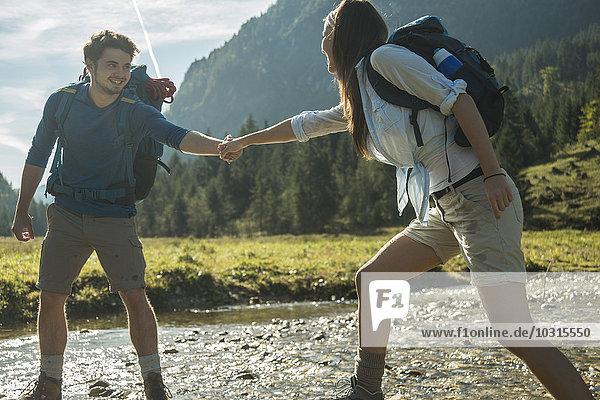 Österreich  Tirol  Tannheimer Tal  zwei junge Wanderer beim Überqueren des Wassers
