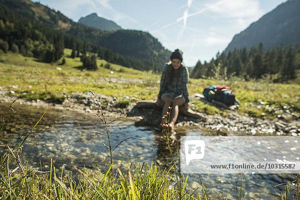 Österreich  Tirol  Tannheimer Tal  junge Wanderin entspannt am Bach
