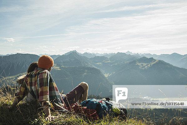 Österreich  Tirol  Tannheimer Tal  junges Paar beim Ausruhen in den Bergen
