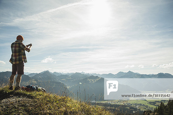 Austria  Tyrol  Tannheimer Tal  young man taking picture in mountainscape