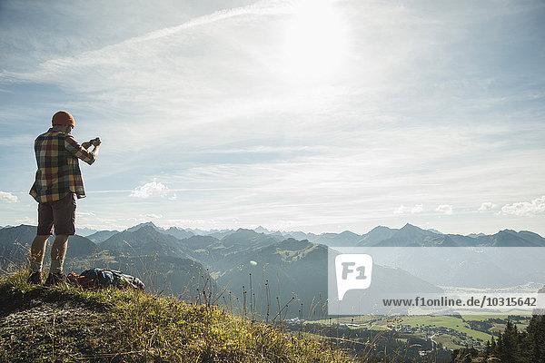 Österreich  Tirol  Tannheimer Tal  junger Mann beim Fotografieren in der Bergwelt