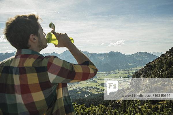 Österreich  Tirol  Tannheimer Tal  junger Mann trinkt Wasser in der Bergwelt