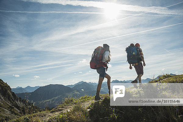Austria  Tyrol  Tannheimer Tal  young couple hiking on mountain trail